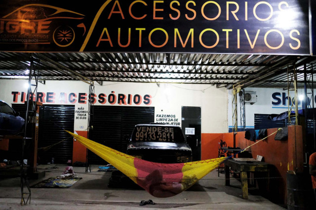 Venezuelan man sleeps on a hammock during the night at the car repair shop, near the interstate Bus Station in Boa Vista, Roraima state, Brazil August 24, 2018. Picture taken August 24, 2018. REUTERS/Nacho Doce