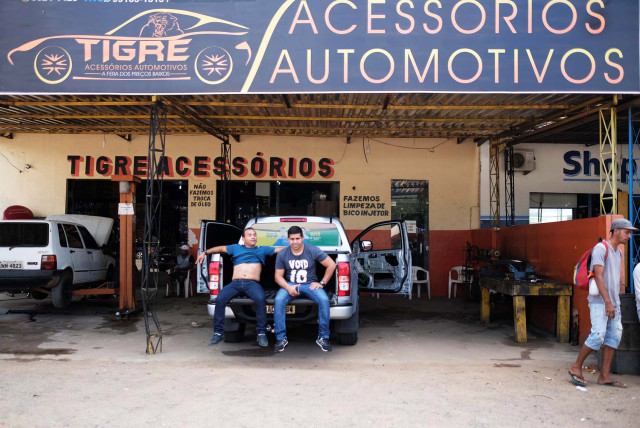 Brazilian men sit on a car as they wait to be attended in the car repair shop, near the interstate Bus Station in Boa Vista, Roraima state, Brazil August 24, 2018. Picture taken August 24, 2018. REUTERS/Nacho Doce