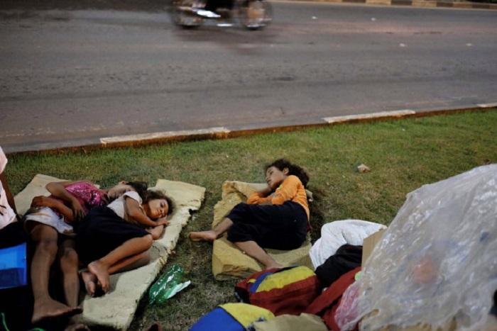 Venezuelan children sleep on the grass in front of interstate Bus Station in Boa Vista, Roraima state, Brazil August 23, 2018. Picture taken August 23, 2018. REUTERS/Nacho Doce
