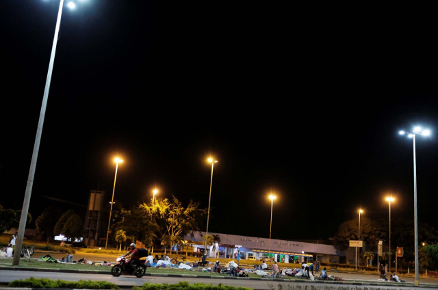 Venezuelan people sleep on the grass in front of interstate Bus Station durinh the night in Boa Vista, Roraima state, Brazil August 23, 2018. Picture taken August 23, 2018. REUTERS/Nacho Doce
