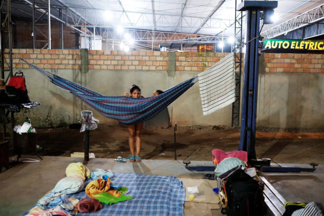 Venezuelan women are pictured near their improvised beds during the night at the car repair shop, near the interstate Bus Station in Boa Vista, Roraima state, Brazil August 24, 2018. Picture taken August 24, 2018. REUTERS/Nacho Doce