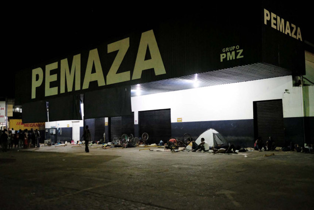 Venezuelan people rest during the night in a spare parts shop for cars and motorbikes, near the interstate Bus Station in Boa Vista, Roraima state, Brazil August 24, 2018. Picture taken August 24, 2018. REUTERS/Nacho Doce