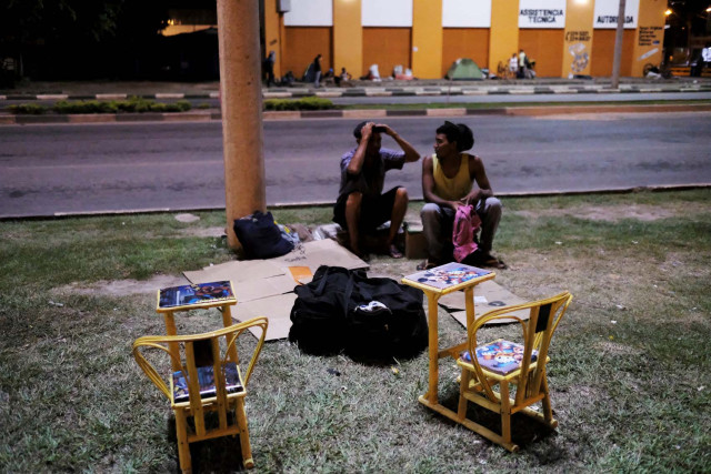 Venezuelan men talks on the grass in front of interstate Bus Station in Boa Vista, Roraima state, Brazil August 25, 2018. Picture taken August 25, 2018. REUTERS/Nacho Doce