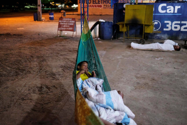 Venezuelan boy sleeps on a hammock during the night at the car repair shop, near the interstate Bus Station in Boa Vista, Roraima state, Brazil August 25, 2018. Picture taken August 25, 2018. REUTERS/Nacho Doce
