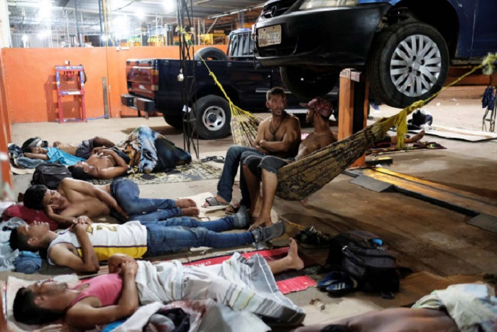 Venezuelan people are pictured on their improvised beds during the night at the car repair shop, near the interstate Bus Station in Boa Vista, Roraima state, Brazil August 25, 2018. Picture taken August 25, 2018. REUTERS/Nacho Doce