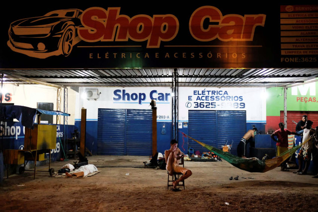 Venezuelan people are pictured near their improvised beds during the night at the car repair shop, near the interstate Bus Station in Boa Vista, Roraima state, Brazil August 25, 2018. Picture taken August 25, 2018. REUTERS/Nacho Doce
