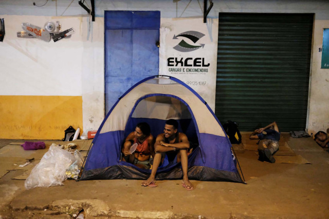Venezuelan people sit on their tent and sleep on cardboards during the night at the entrance of packages transport shop in front of the interstate Bus Station in Boa Vista, Roraima state, Brazil August 25, 2018. Picture taken August 25, 2018. REUTERS/Nacho Doce