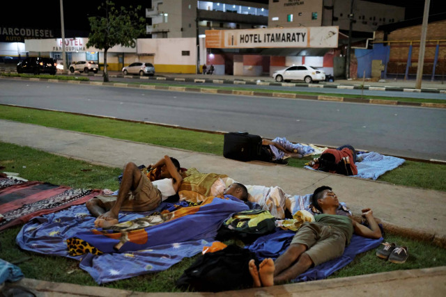 Venezuelan men sleep on the grass in front of interstate Bus Station in Boa Vista, Roraima state, Brazil August 24, 2018. Picture taken August 24, 2018. REUTERS/Nacho Doce
