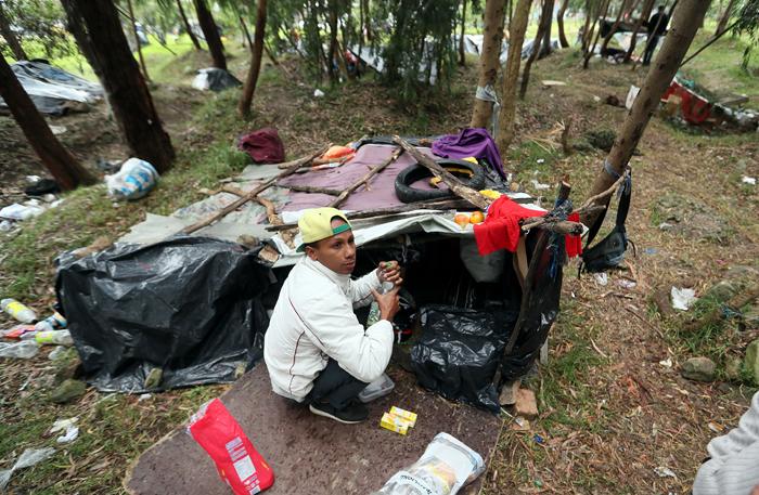 ACOMPAÑA CRÓNICA: COLOMBIA VENEZUELA ÉXODO. BOG200. BOGOTÁ (COLOMBIA), 07/09/2018.- Fotografía del 6 de septiembre de 2018 que muestra a un ciudadano venezolano mientras prepara el desayuno bajo plásticos y lonas en un terreno arbolado de Bogotá (Colombia). La terminal de autobuses de Bogotá es un huracán de viajeros y vehículos, pasajeros que se despiden entre sonrisas y lágrimas con esperanzas e ilusiones; sueños como el de más de un centenar de venezolanos que acampan en un parque cerca a la estación mientras esperan un futuro mejor. EFE/Mauricio Dueñas Castañeda