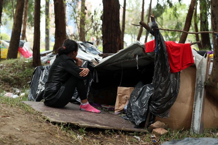 ACOMPAÑA CRÓNICA: COLOMBIA VENEZUELA ÉXODO. BOG202. BOGOTÁ (COLOMBIA), 07/09/2018.- Fotografía del 6 de septiembre de 2018 que muestra a una ciudadana venezolana frente a la carpa en la que duerme en un terreno arbolado de Bogotá (Colombia). La terminal de autobuses de Bogotá es un huracán de viajeros y vehículos, pasajeros que se despiden entre sonrisas y lágrimas con esperanzas e ilusiones; sueños como el de más de un centenar de venezolanos que acampan en un parque cerca a la estación mientras esperan un futuro mejor. EFE/Mauricio Dueñas Castañeda
