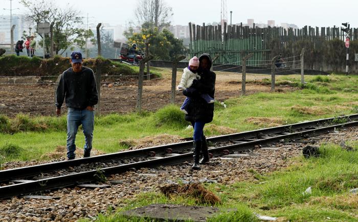 ACOMPAÑA CRÓNICA: COLOMBIA VENEZUELA ÉXODO. BOG208. BOGOTÁ (COLOMBIA), 07/09/2018.- Fotografía del 6 de septiembre de 2018 que muestra a ciudadanos venezolanos mientras cruzan una vía férrea en Bogotá (Colombia). La terminal de autobuses de Bogotá es un huracán de viajeros y vehículos, pasajeros que se despiden entre sonrisas y lágrimas con esperanzas e ilusiones; sueños como el de más de un centenar de venezolanos que acampan en un parque cerca a la estación mientras esperan un futuro mejor. EFE/Mauricio Dueñas Castañeda