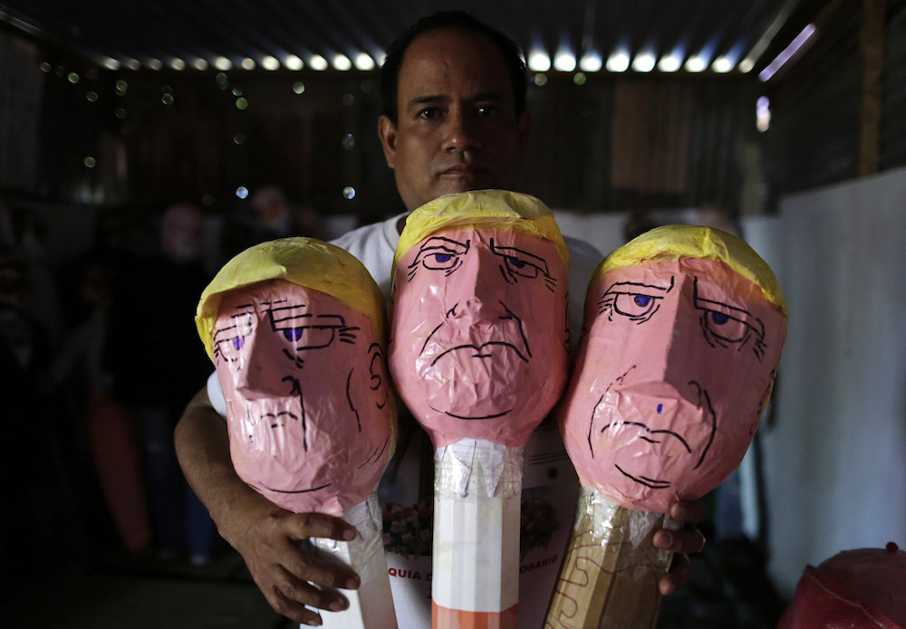 A local craftsman displays his handmade puppets of United States President Donald Trump ahead of New Year's Eve in Managua, on December 29, 2018. - The puppets, made from old clothes to represent the past year, are traditionally burned at the New Year as a way of saying goodbye to the old year and welcoming the new. (Photo by INTI OCON / AFP)